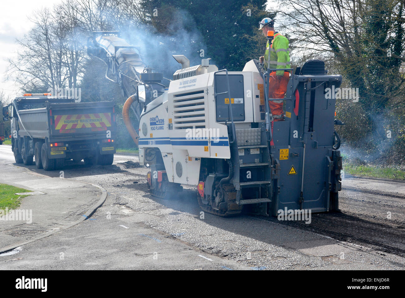 Defective & worn out asphalt road being planed off in preparation for repaving tipper truck loading waste for - Stock Image