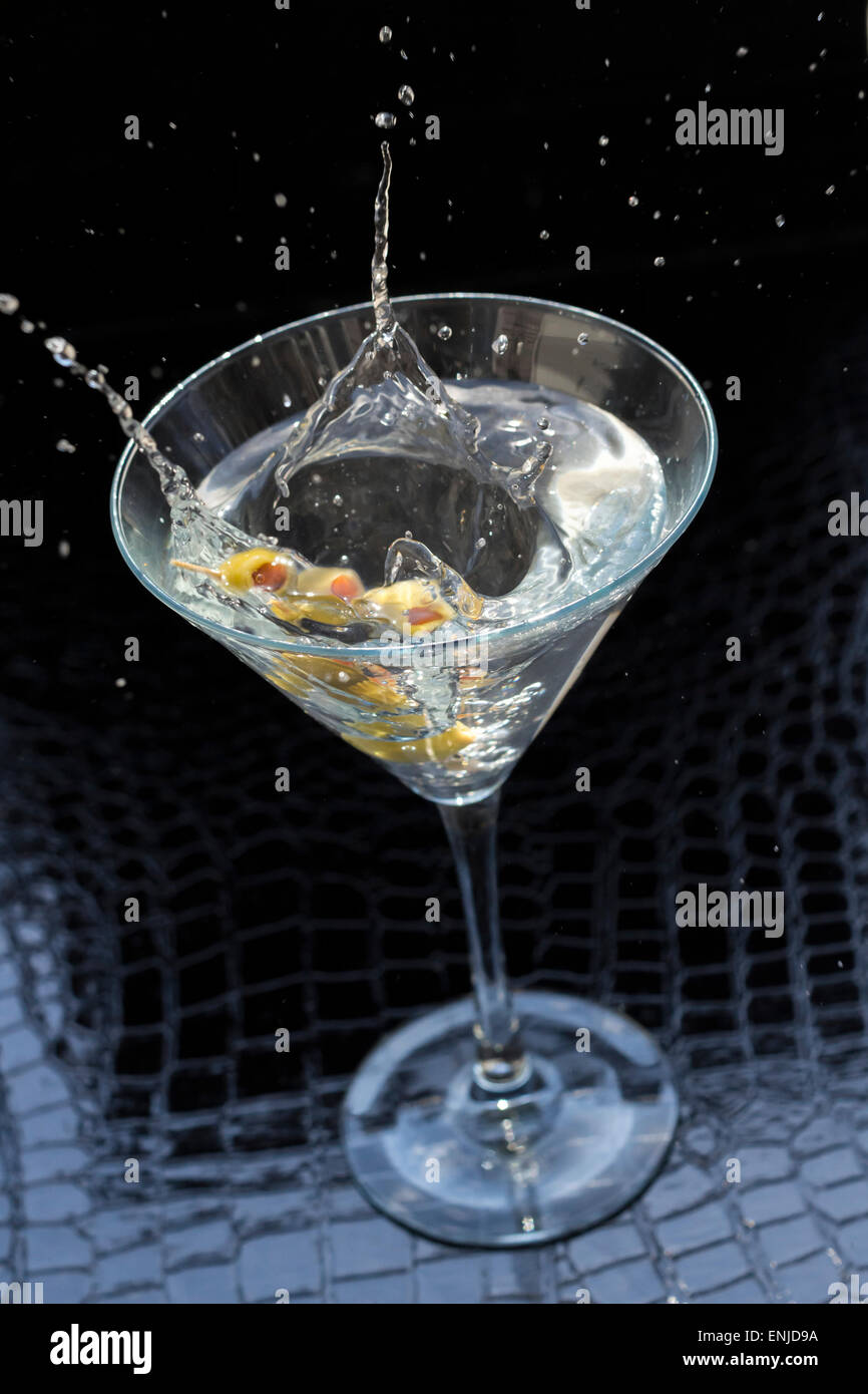 Splashing dirty martini garnished with green olives on toothpick - Stock Image