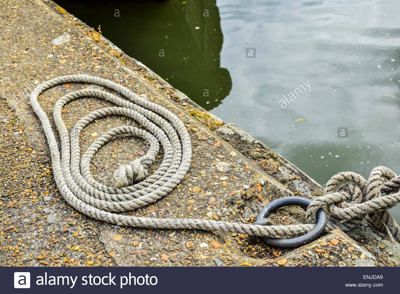 A coil of rope next to a boat mooring - Stock Image