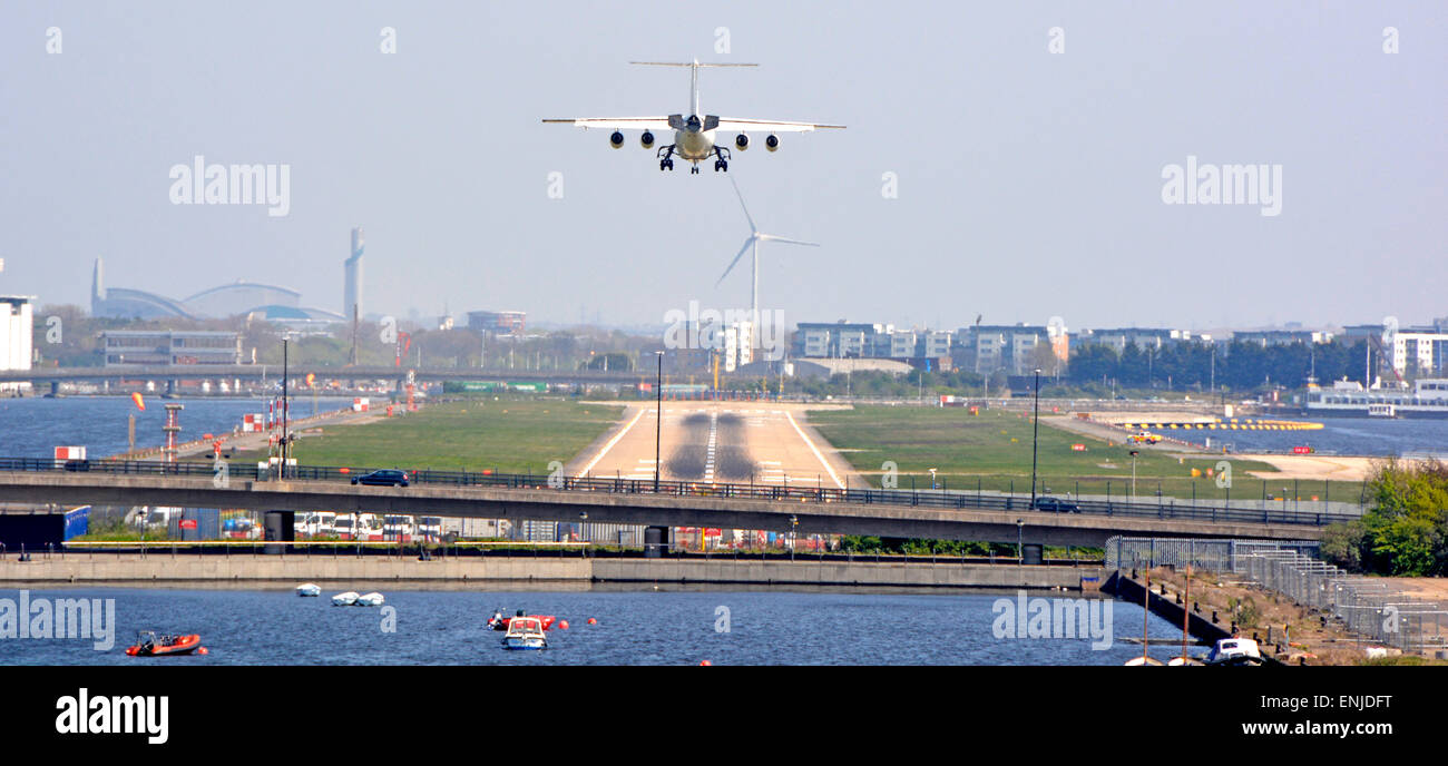 London City Airport four engined passenger jet aircraft approaching runway in middle of old London Docklands waters - Stock Image