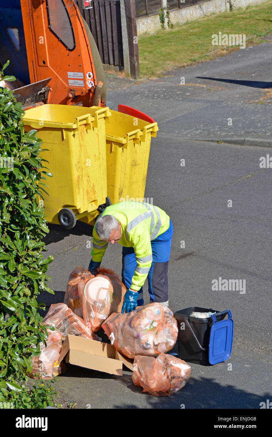 Dustman at rear of refuse truck picking up household rubbish designated as recyclable by placing in orange plastic - Stock Image
