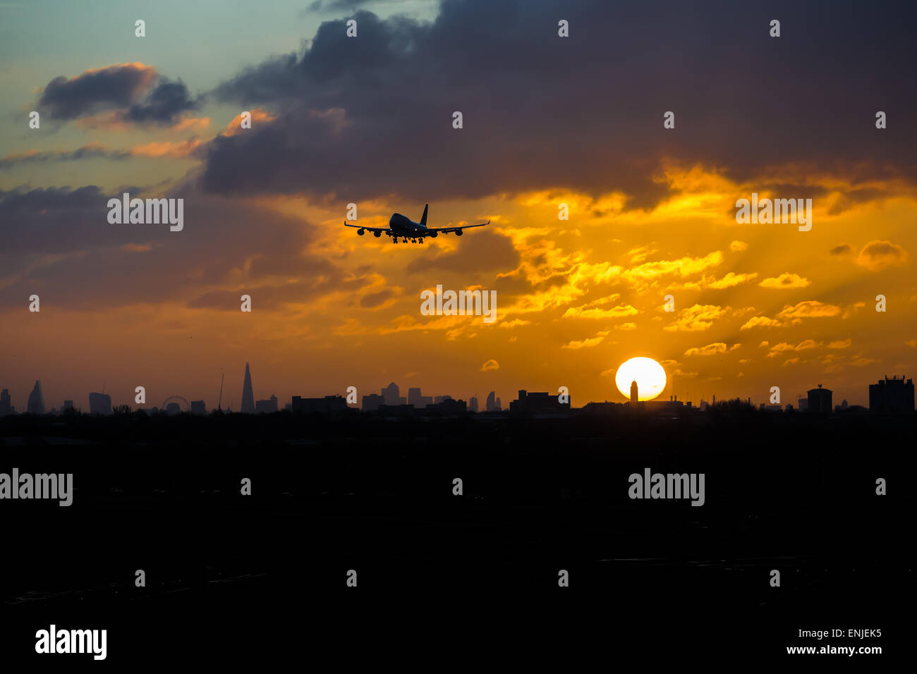 A plane comes into land at Heathrow Airport, London, United Kingdom as the sun rises above London City skyline - Stock Image