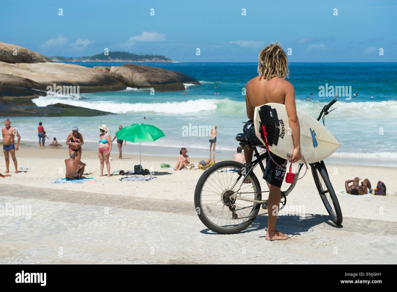 RIO DE JANEIRO, BRAZIL - FEBRUARY 2015: Brazilian surfer on a bike sits looking out at the waves at Arpoador. - Stock Image