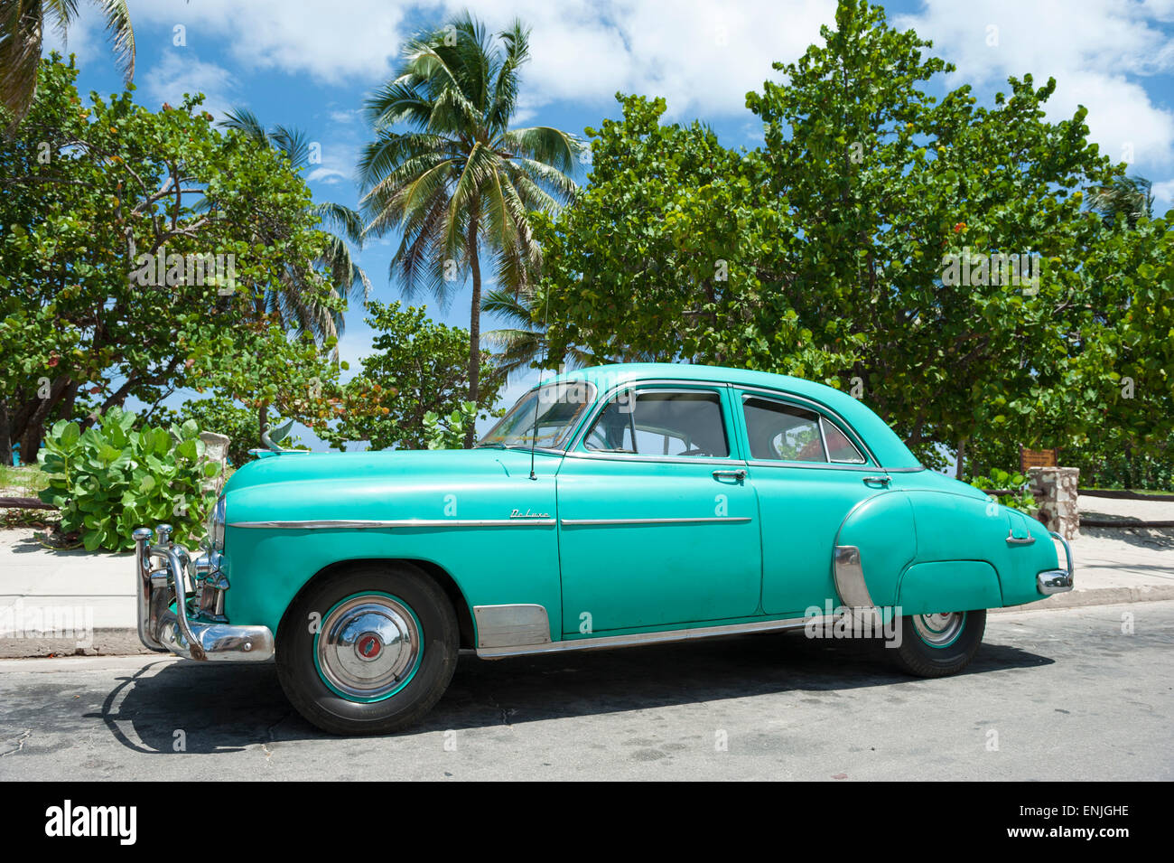Classic vintage American car in bright tropical turquoise blue with ...