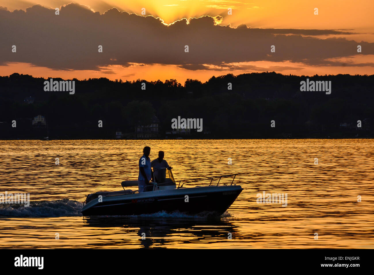 picturesque sunset over Lake Starnberg near Schloss Berg with the silhouette of a motorboat and the reflexion of - Stock Image