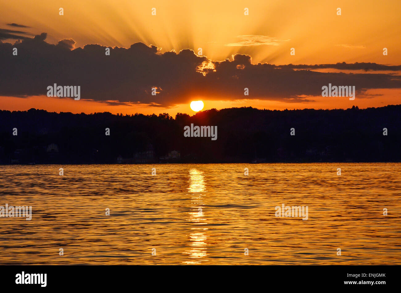 picturesque sunset over Lake Starnberg near Schloss Berg with the reflexion of the sun on the rippled water surface - Stock Image