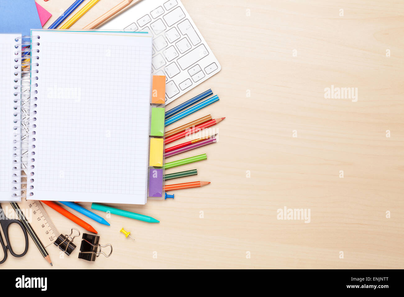 Blank notepad over school and office supplies on office table Top