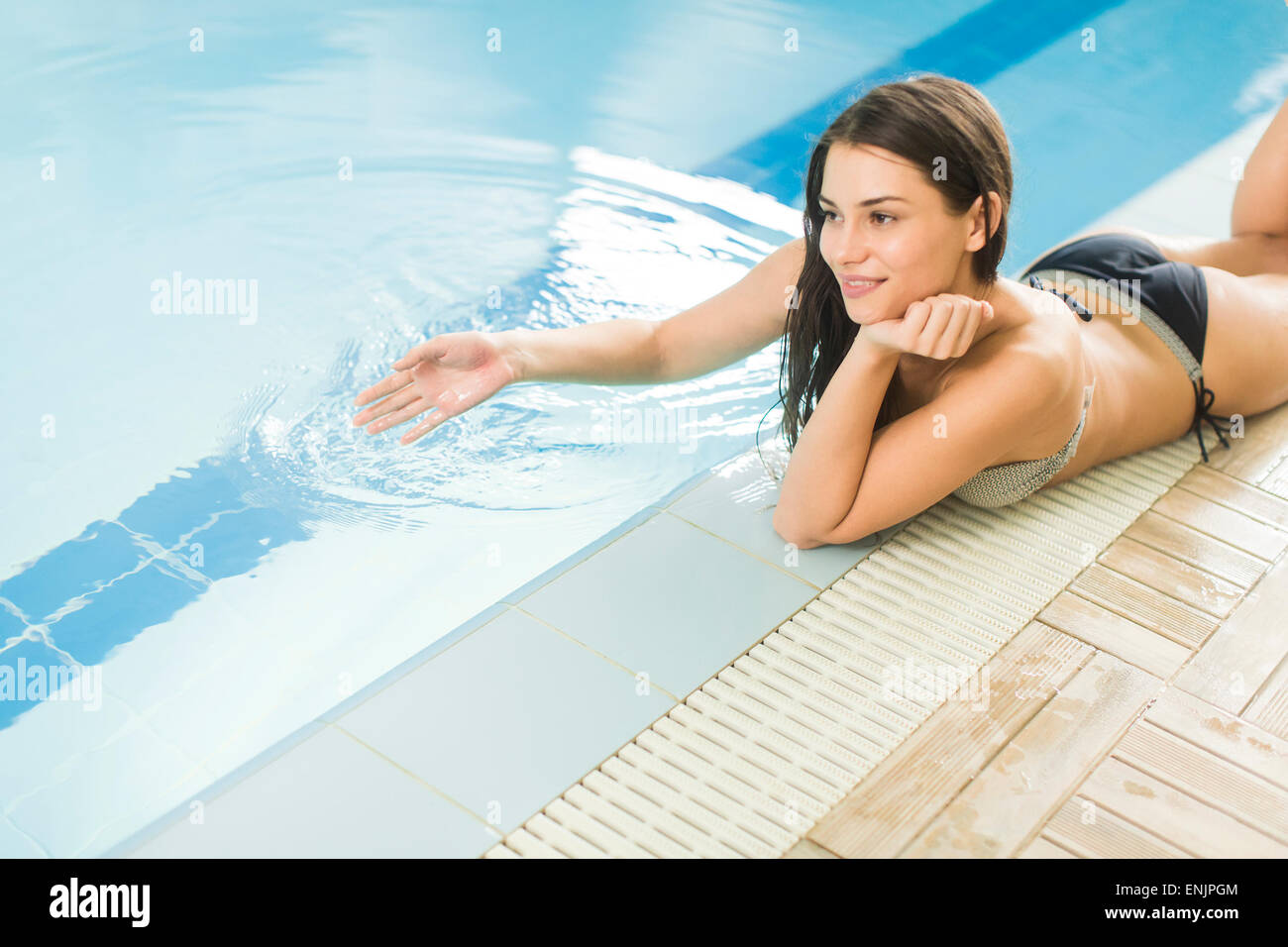 Pretty young woman by the pool - Stock Image