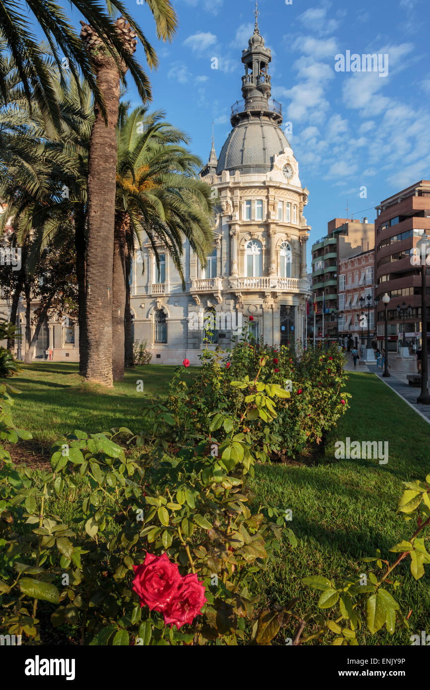 Town Hall under a cloud dappled blue sky with palm trees and roses, Cartagena, Murcia Region, Spain, Europe - Stock Image