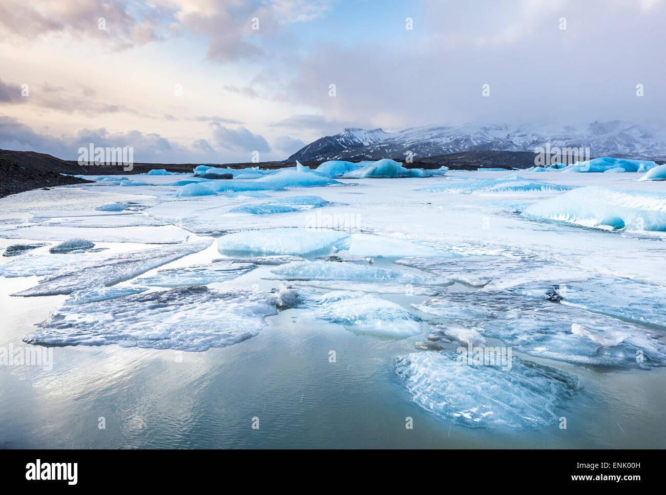 Frozen icebergs locked in the frozen waters of Fjallsarlon Glacier lagoon, South East Iceland, Iceland, Polar Regions - Stock Image