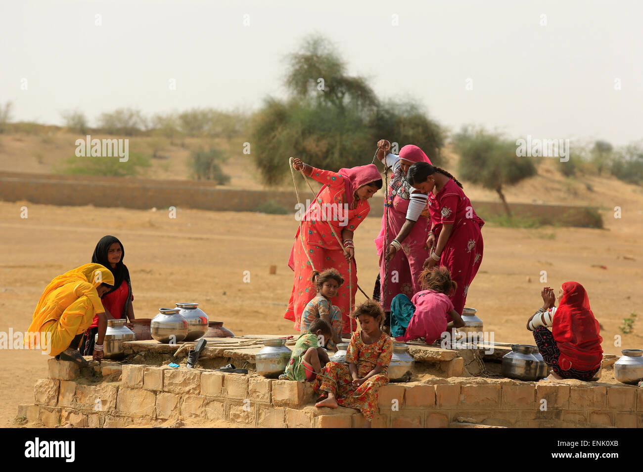 JAISALMER,INDIA - November 9,2014 : Unidentified women draw water form the well and take it to their home. - Stock Image
