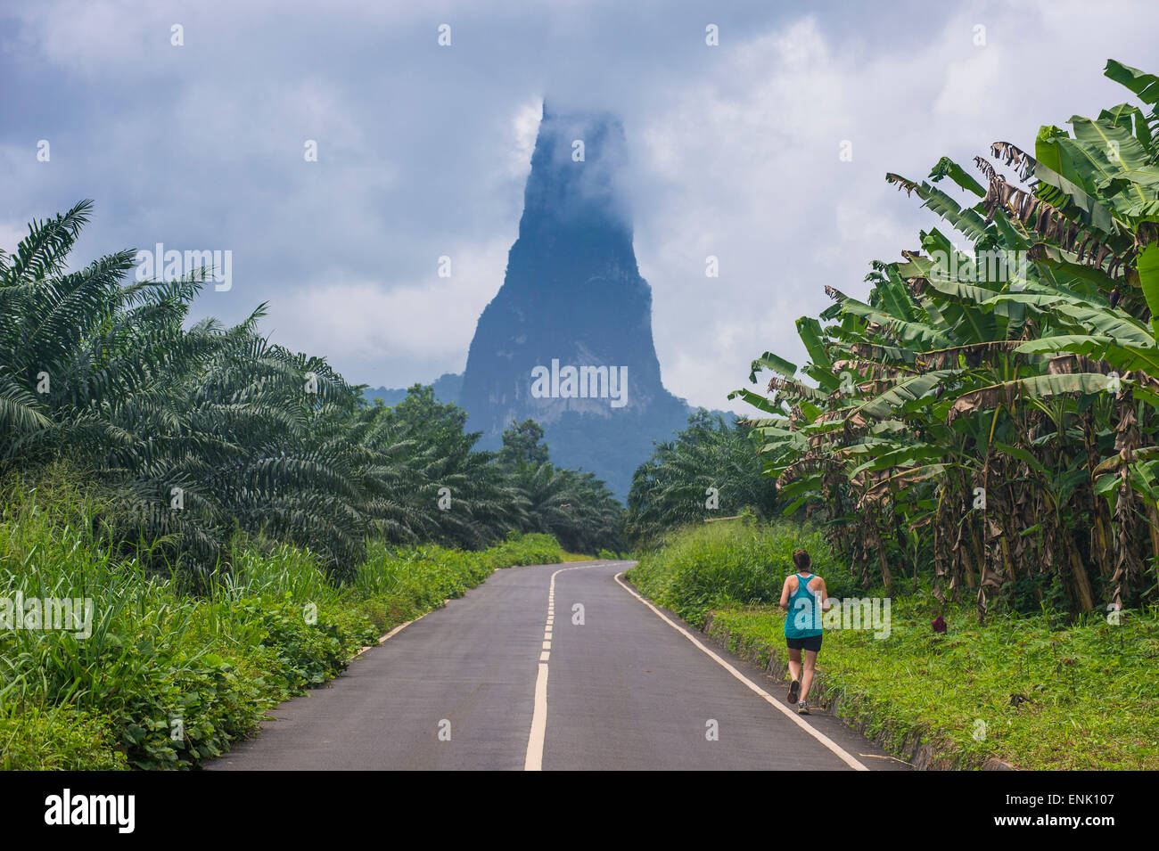 Runner on a road leading to the unusal monolith, Pico Cao Grande, east coast of Sao Tome, Sao Tome and Principe, - Stock Image