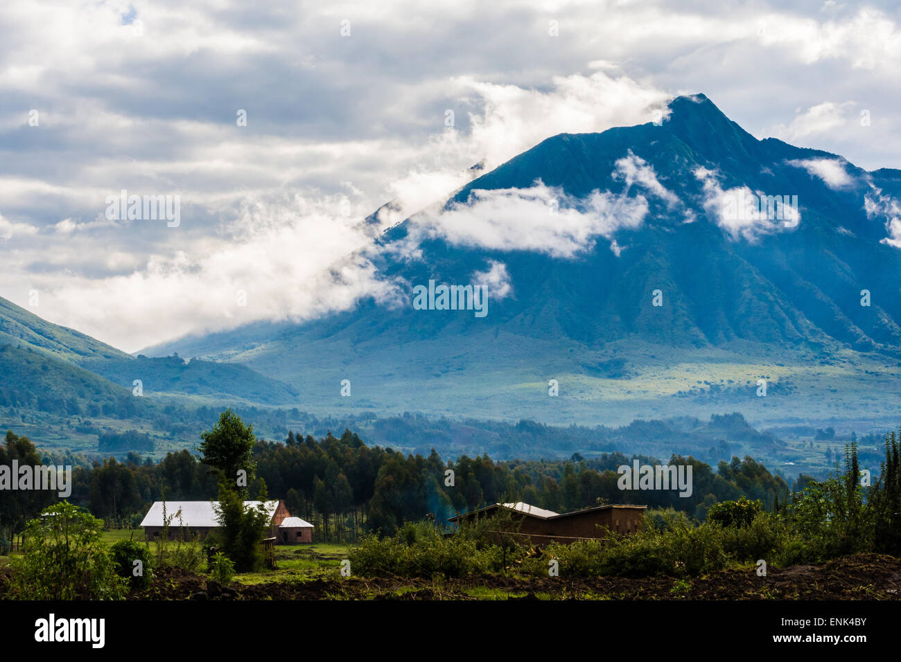 Houses, mountains, and clouds in Parc National des Volcans, Rwanda - Stock Image