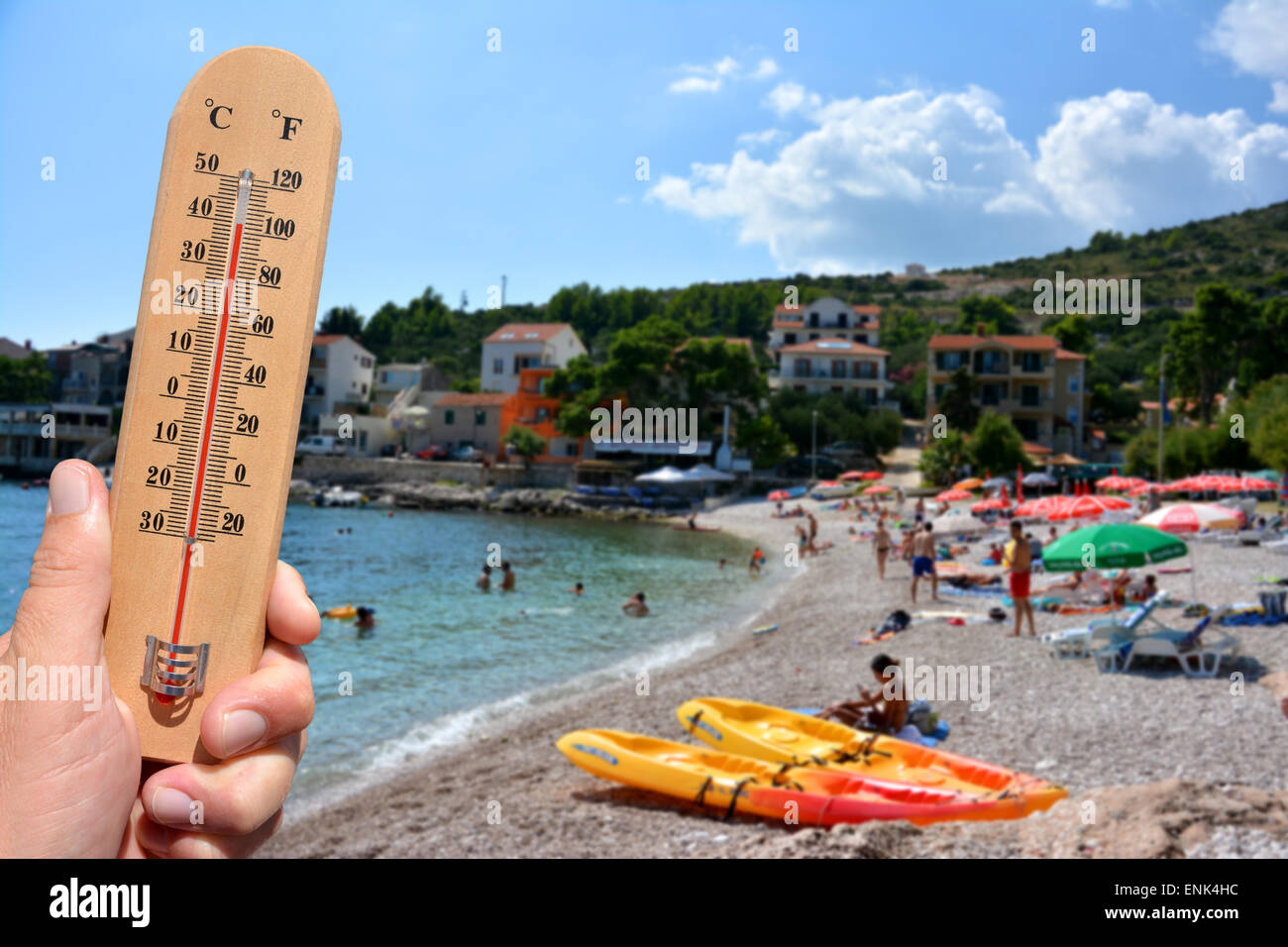 A thermometer scale shows extreme high temperatures during a heat wave and beach in background. Skin cancer warning - Stock Image