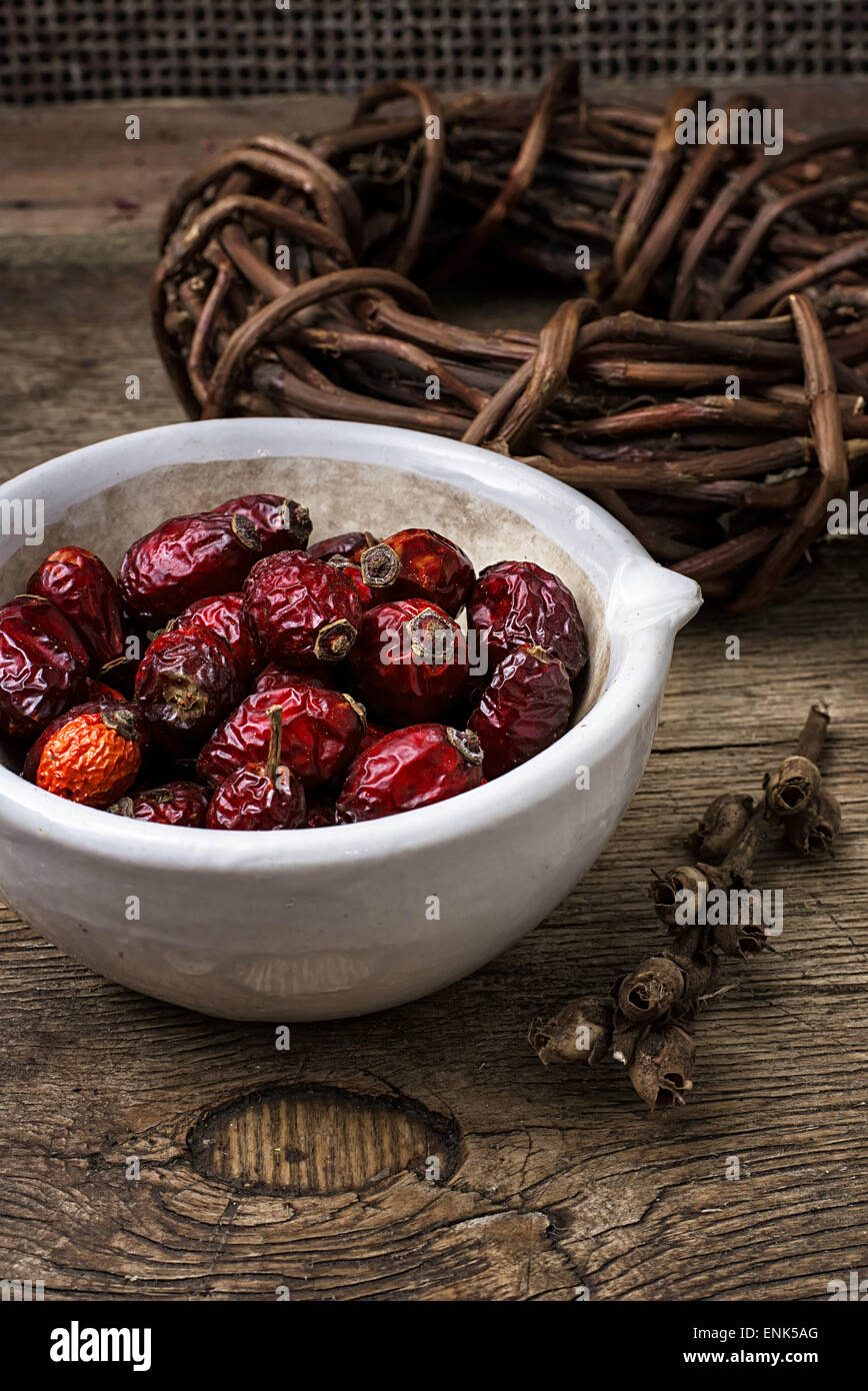 rose in white bowl on background licorice root bound in coil.Selective focus - Stock Image