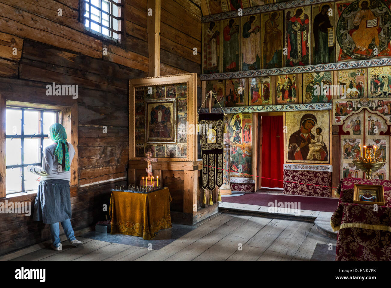 Russia, Kishi island on the lake Onega, open air Museum of Karelian Wooden Architecture, a lady near the window - Stock Image