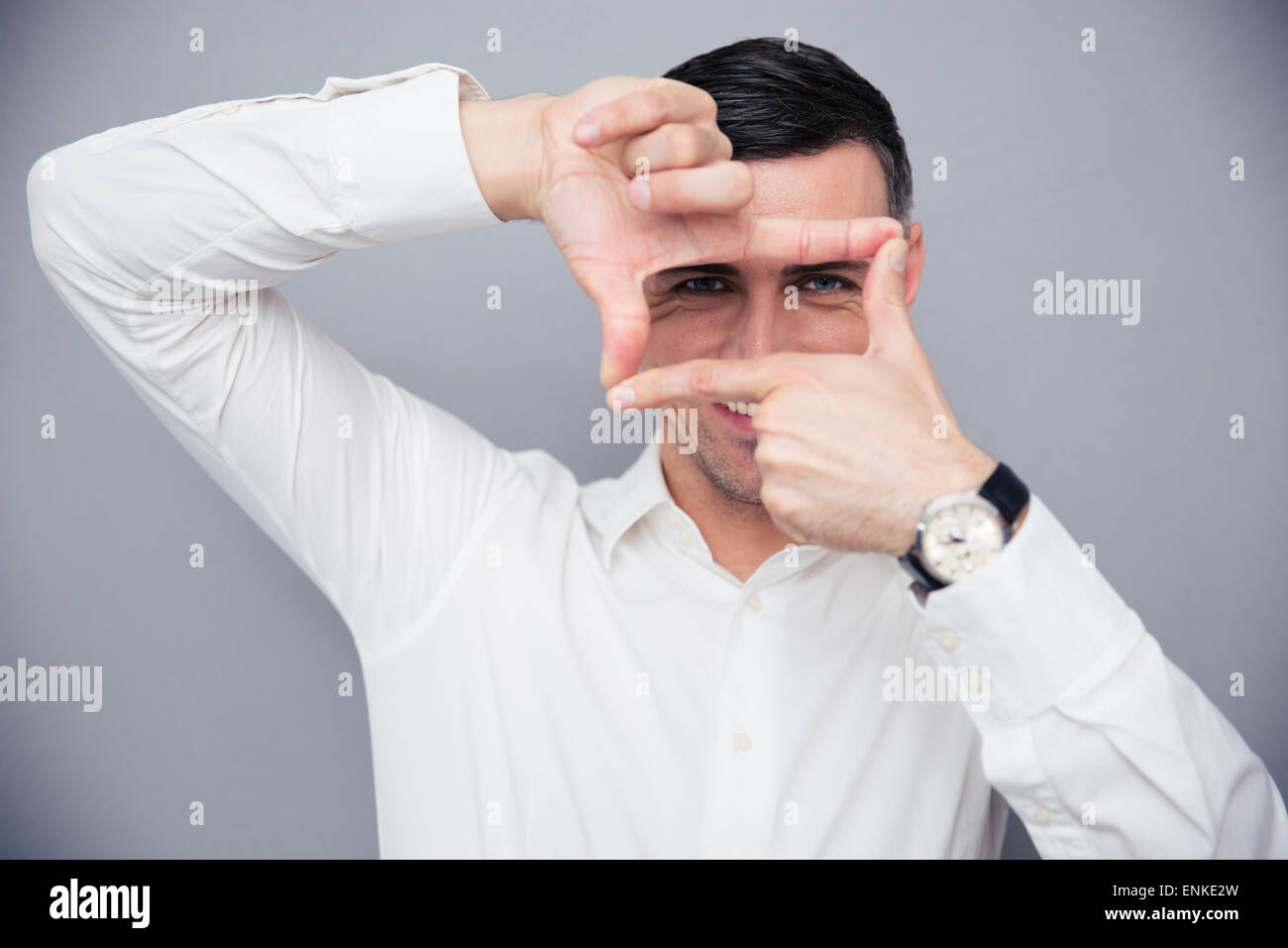 Happy businessman making frame with fingers over gray background and looking at camera - Stock Image