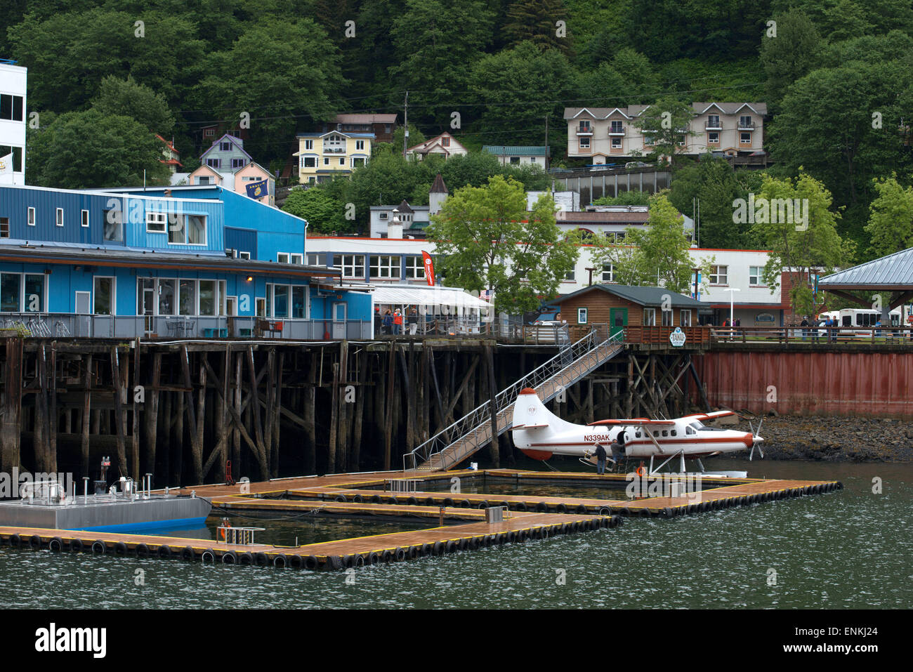 Sightseeing seaplanes parked at the water front in Juneau dock Alaska. Downtown Juneau sits snugly between Mount Stock Photo