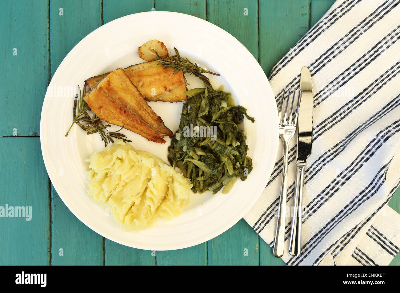 Grilled smoked haddock fillets with rosemary brunches mash potato and swiss chard on white plate, striped cloth - Stock Image