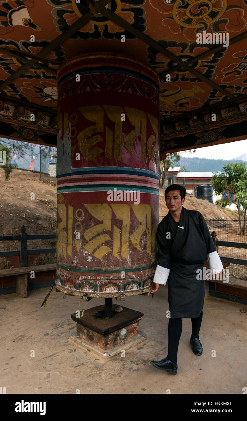 Young Bhutanese spinning a prayer wheel at Chime (or Chimmi) Lhakhang or Mad Monk monastery Buthan - Stock Image