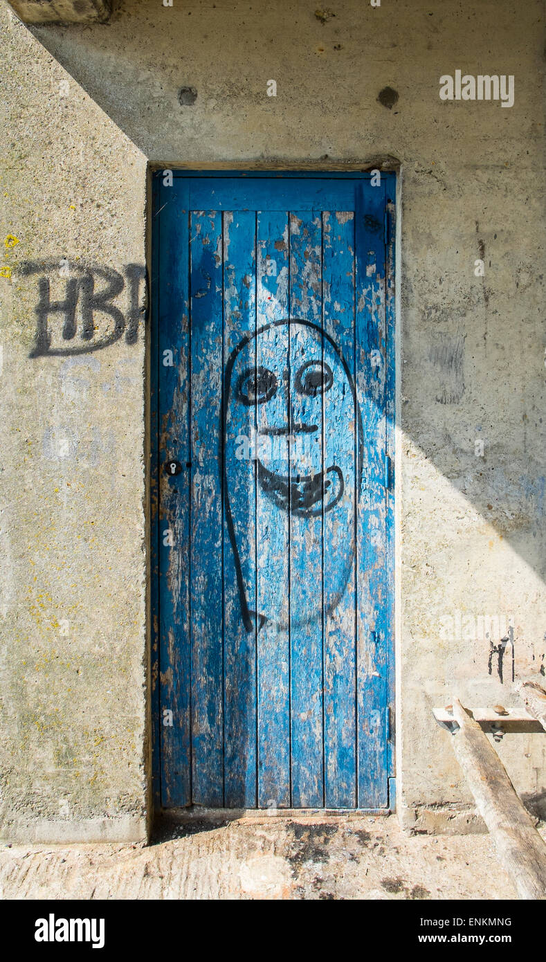 A door with peeling blue paint and primitive face graffiti - Stock Image