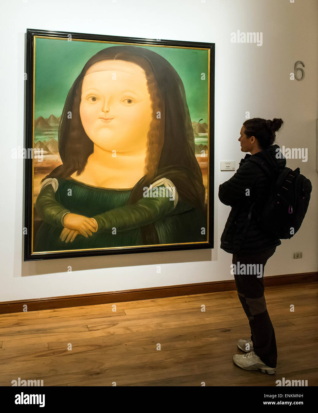 Woman standing by Mona Lisa Monalisa painting by Fernando Botero at Botero Museum Bogota Colombia - Stock Image
