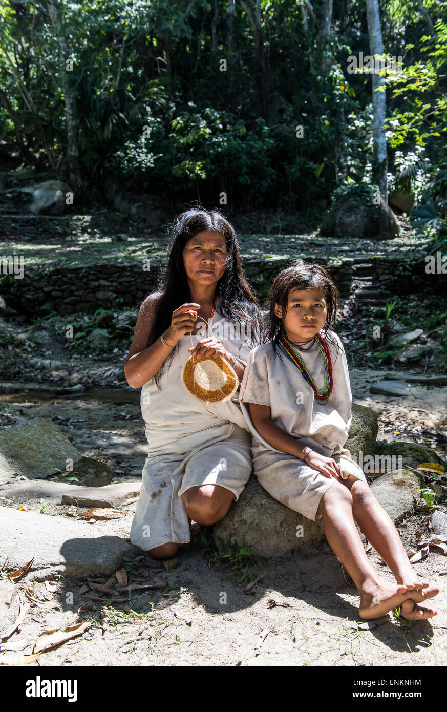 Kogi or Cogui or Kagaba mum knitting with young girl Tayrona National Park Santa Marta Colombia - Stock Image