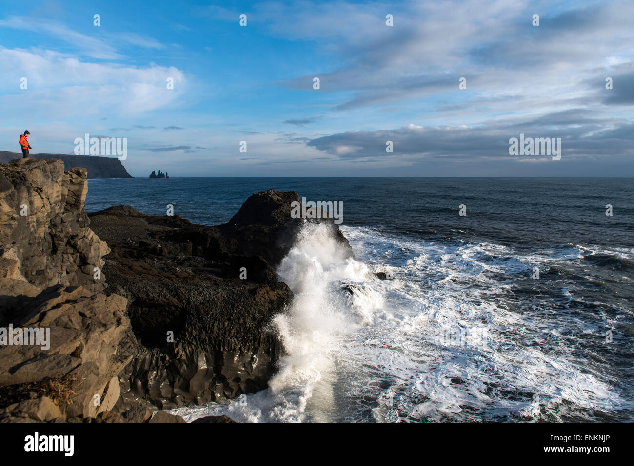 Man standing on the cliff and waves crashing at Dyrhólaey cape South Iceland - Stock Image