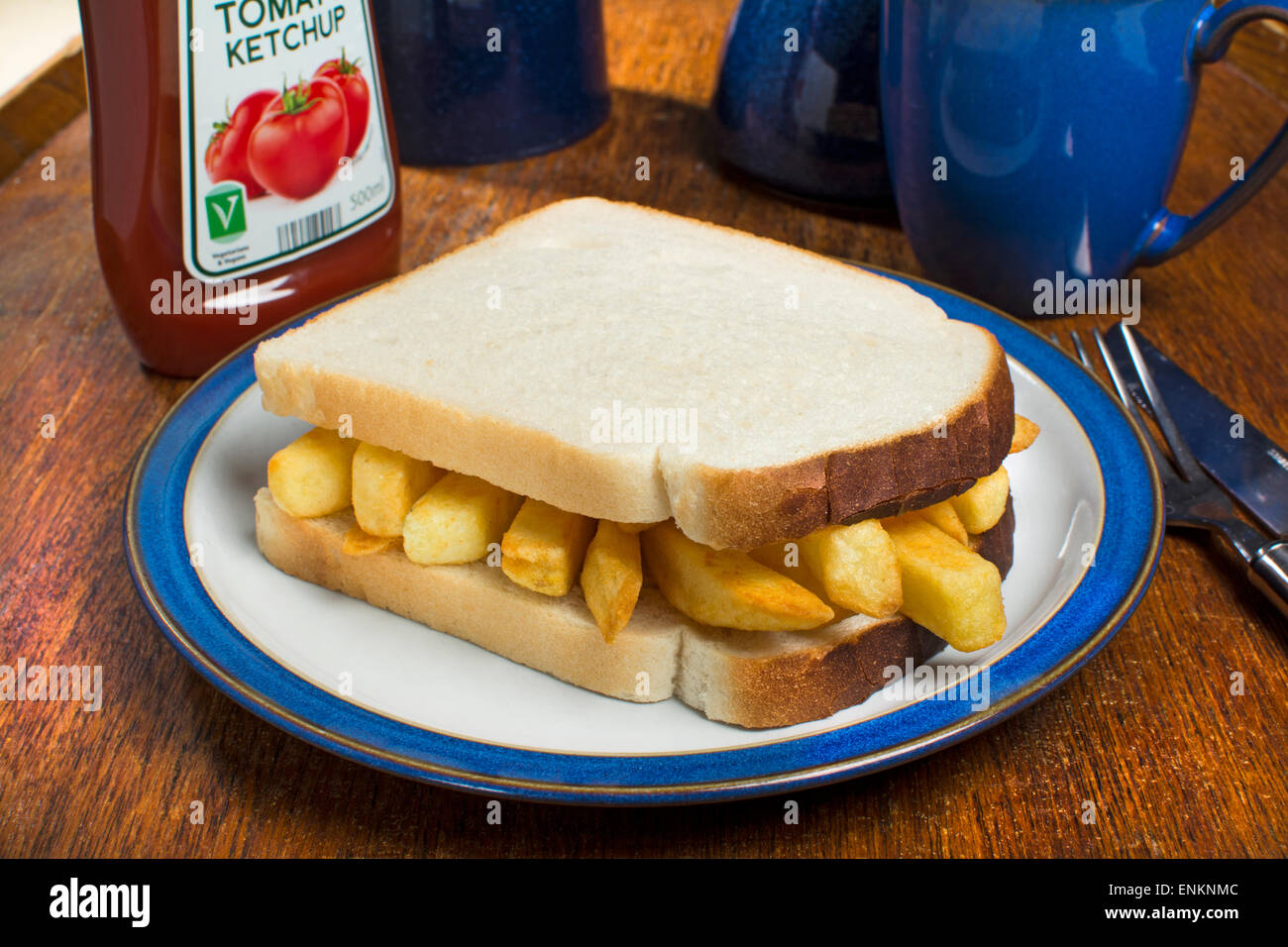 A potato chips sandwich, commonly known as a chip butty in the UK - Stock Image