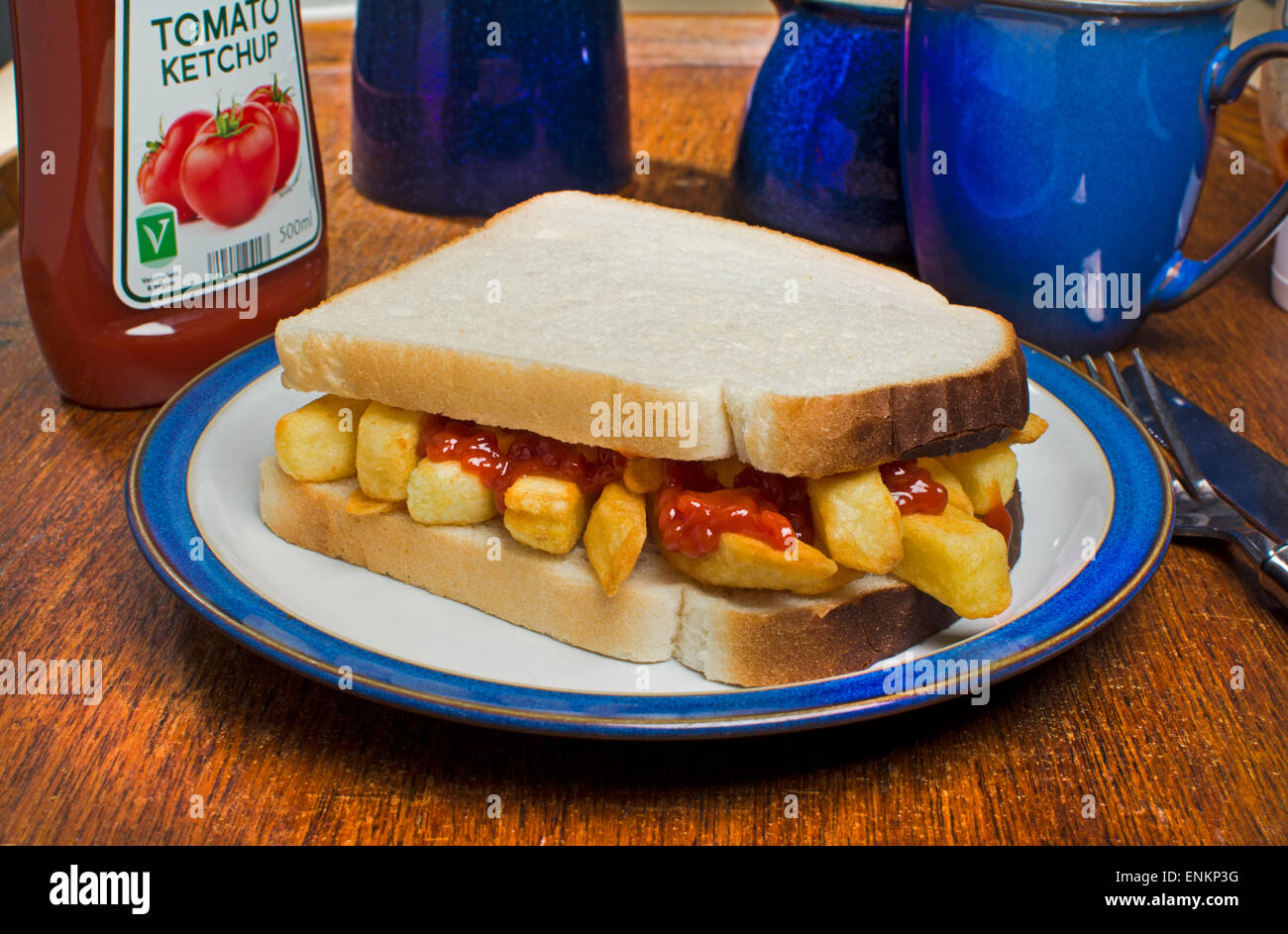A potato chips sandwich, commonly known as a chip butty in the UK, with tomato ketchup sauce - Stock Image