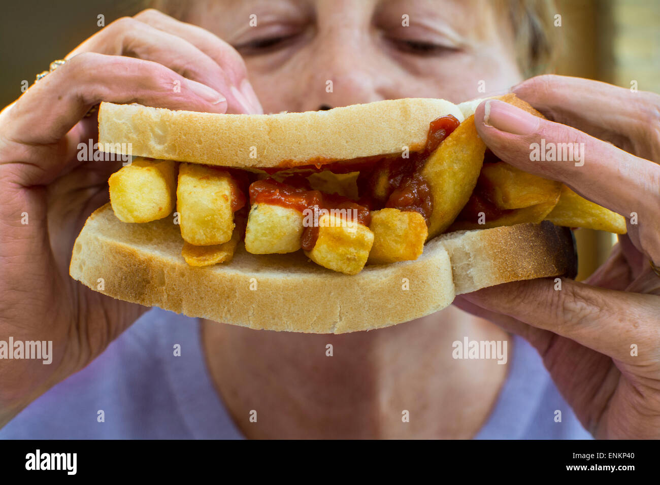 A potato chips sandwich, commonly known as a chip butty in the UK being eaten by a woman - Stock Image