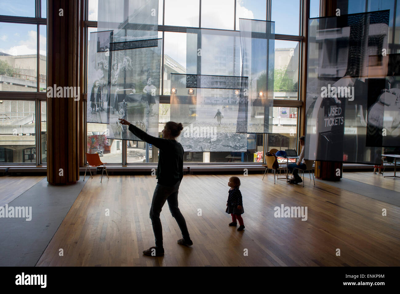 A young child beneath  large screen images showing childhood of a bygone era in Britain's history, on display - Stock Image
