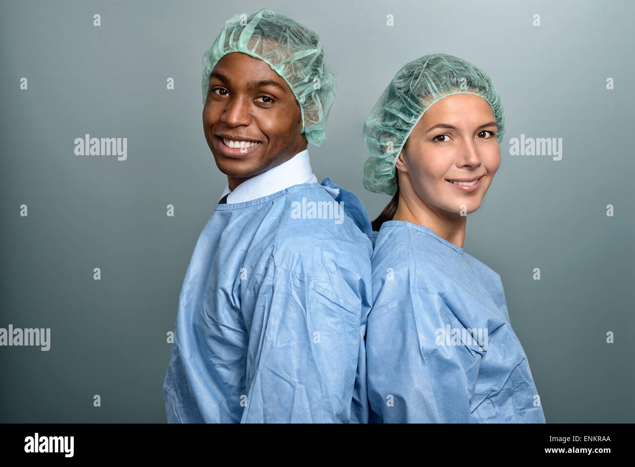 Handsome young African doctor or male nurse in scrubs and a sterility cap looking directly at the camera over a - Stock Image