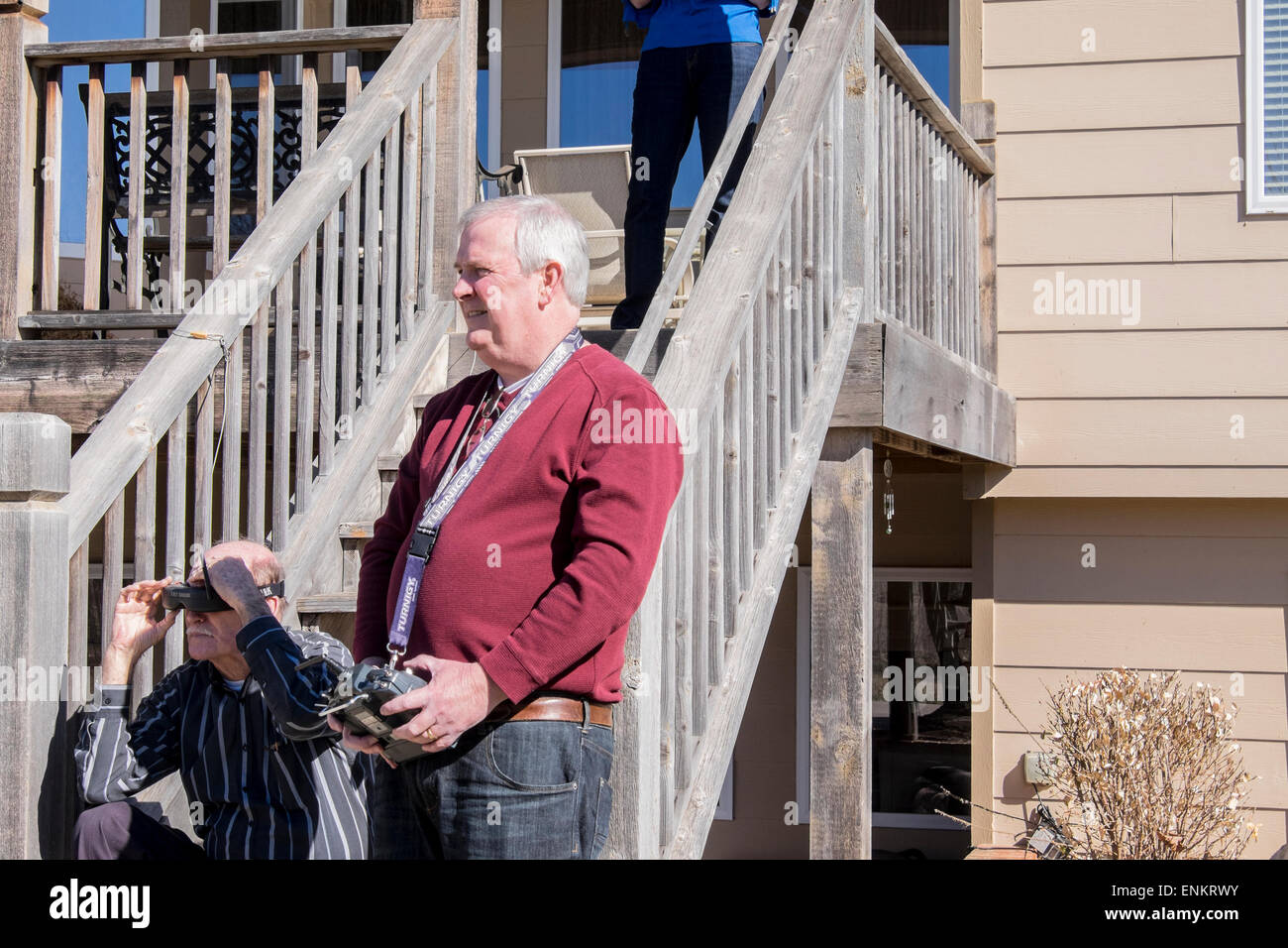 A man flies his quadcopter, while a senior man uses FatShark goggles to visualize the flight. Wichita, Kansas, USA. - Stock Image