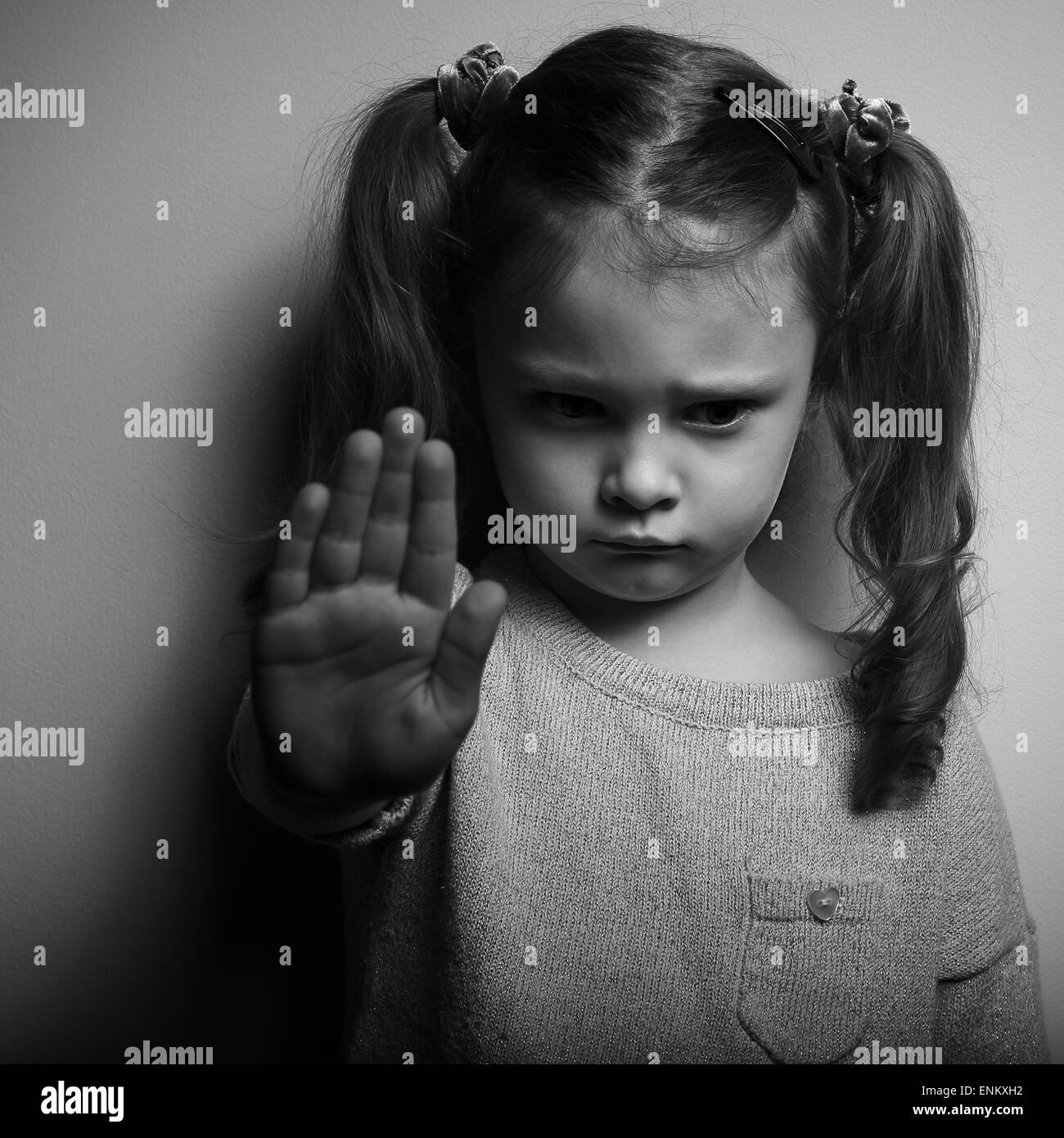 Kid girl showing hand signaling to stop violence and pain and looking down with sad face. Black and white portrait - Stock Image