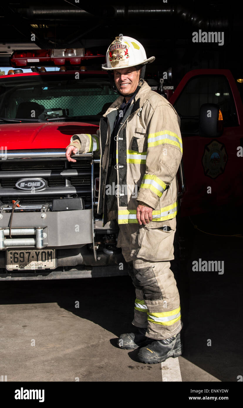 firefighter commander in bunker gear next to command truck - Stock Image