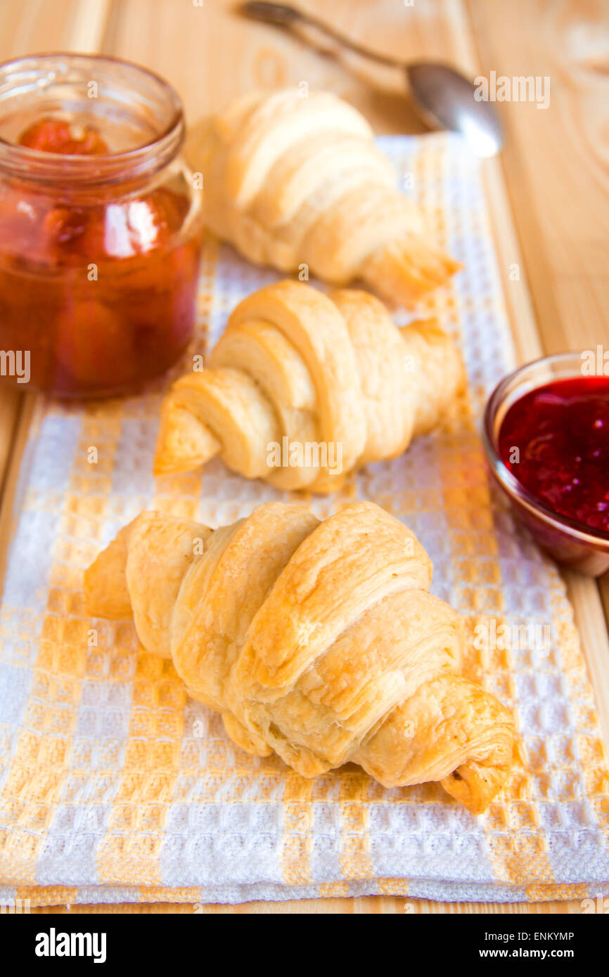 Homemade fresh croissants with jam (marmalade) on napkin and wooden table - Stock Image
