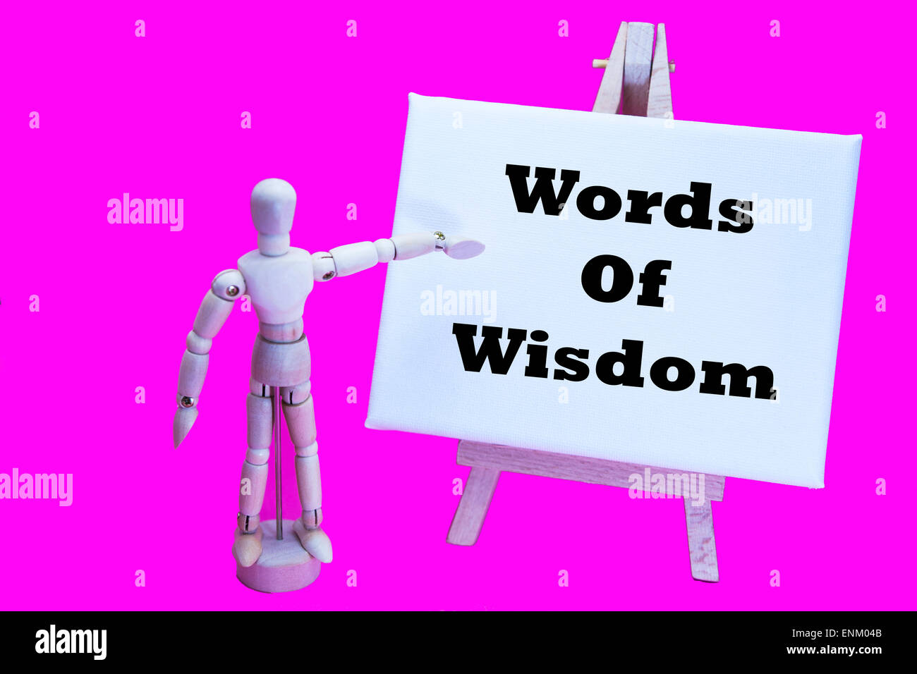 Wooden man with white board pointing at words 'words of wisdom' useful advice help advising helping talking - Stock Image