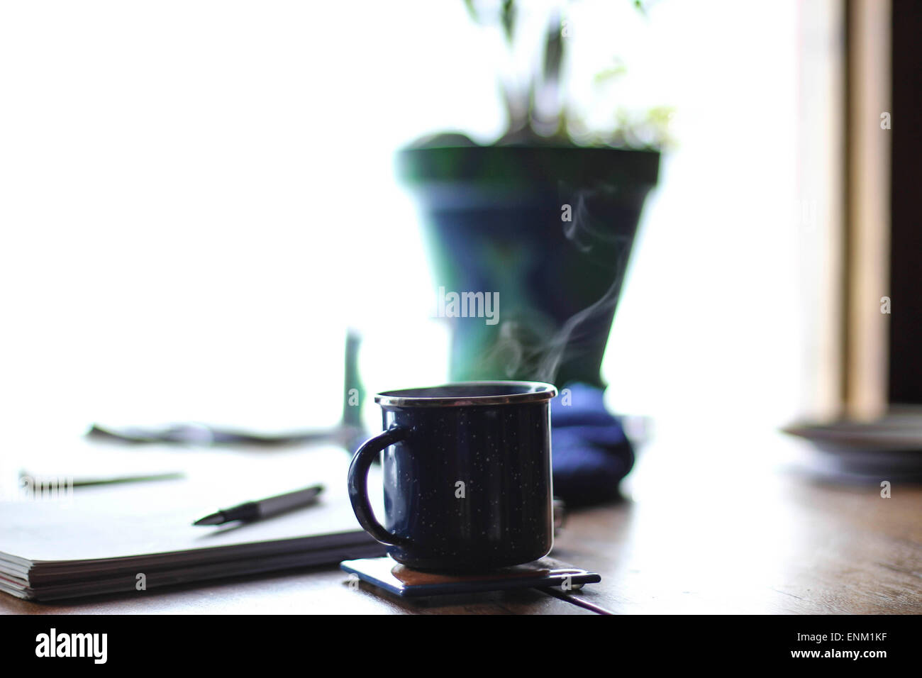 A cup of hot tea sits at a writer's desk - Stock Image