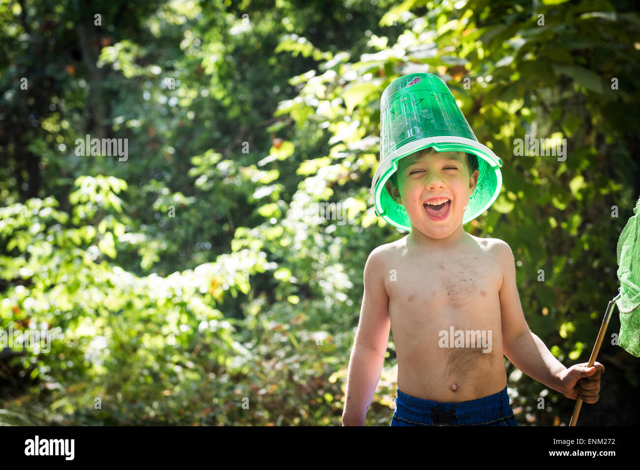 Toddler boy jokes with a bucket on his head and butterfly net in hand while next to creek in Bidwell Park, Chico, - Stock Image