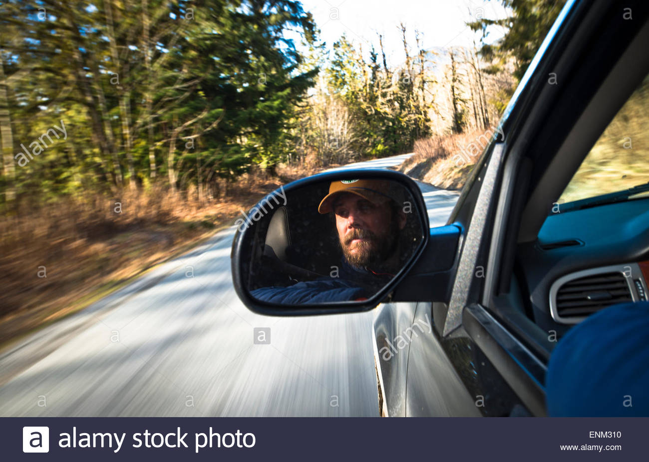 A mans face reflecting in his rear view mirror while driving. - Stock Image