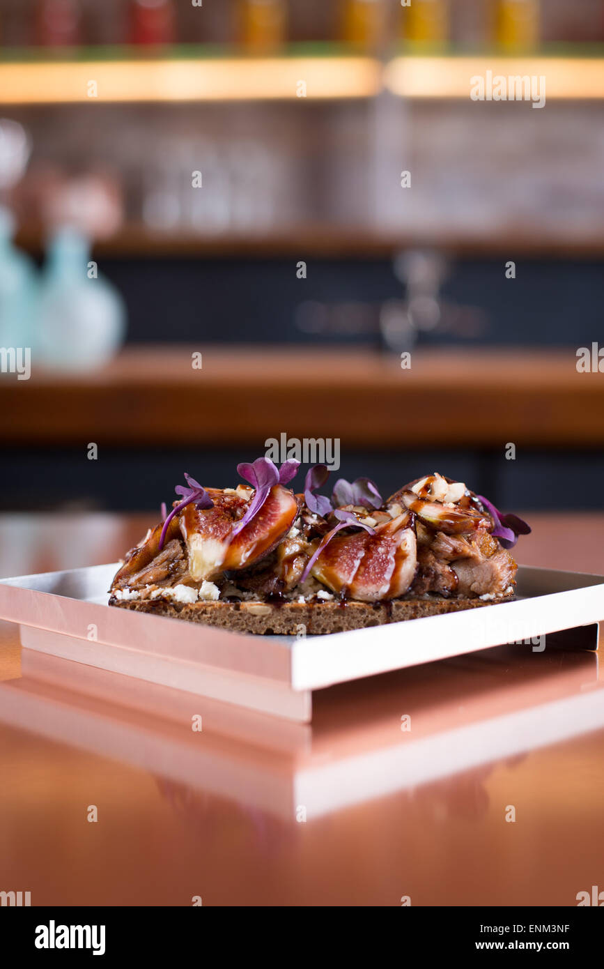 An open-faced sandwich of fig, feta, bacon, and balsamic glaze on brown rye bread with a rainbow micro-green garnish. - Stock Image