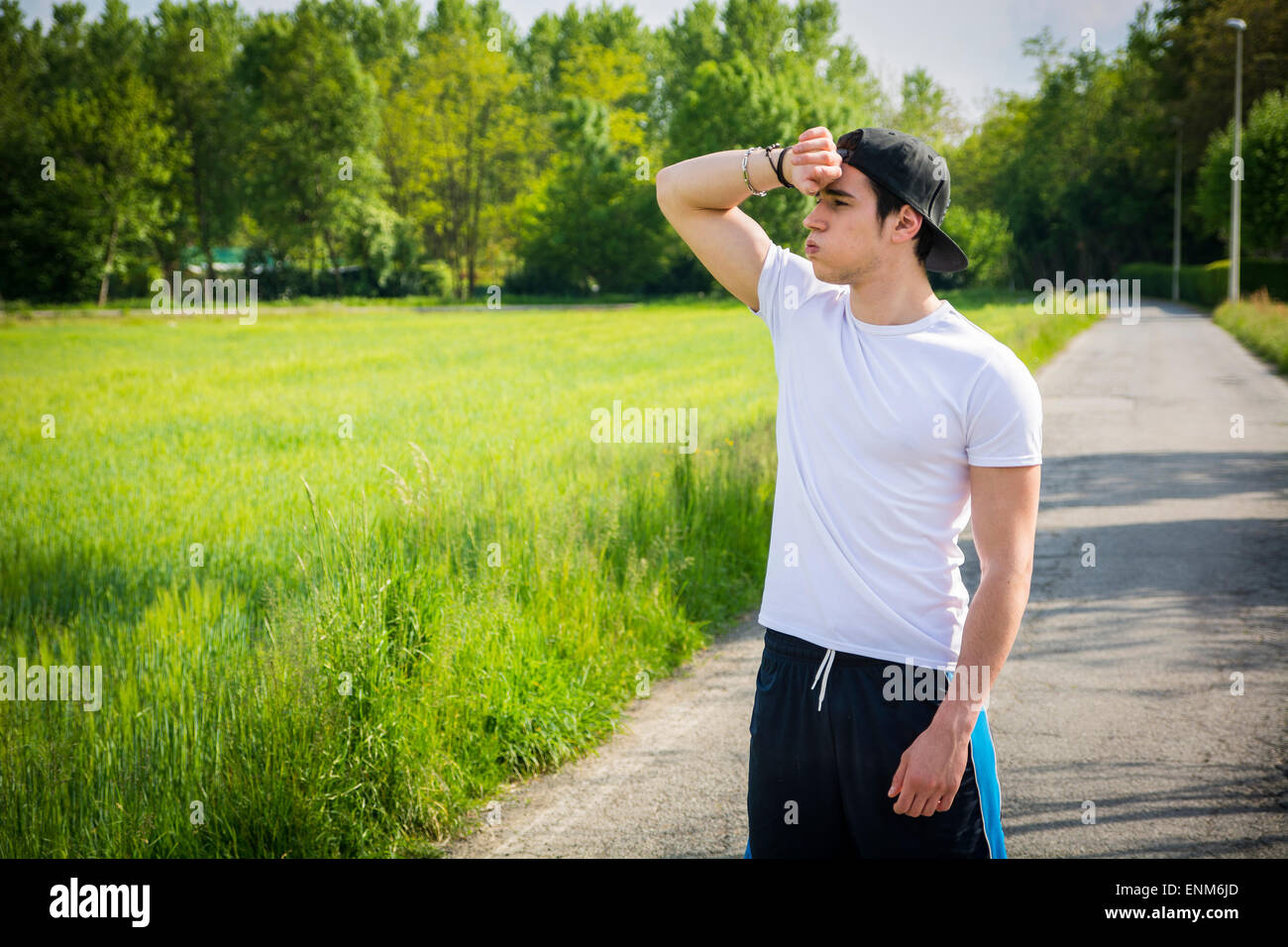Young man resting standing in middle of the road after running - Stock Image