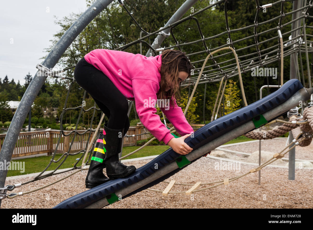 Young girl climbing up a swiveling board at a children's playground - Stock Image