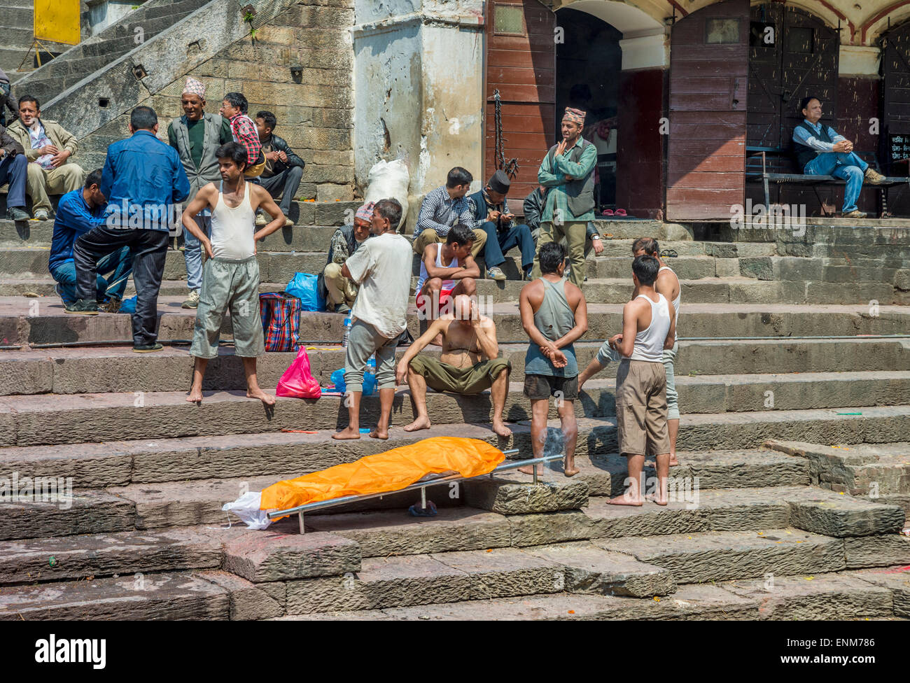 Pashupatinath Temple in Kathmandu. A family is waiting for a cremation ceremony next to a dead body. - Stock Image