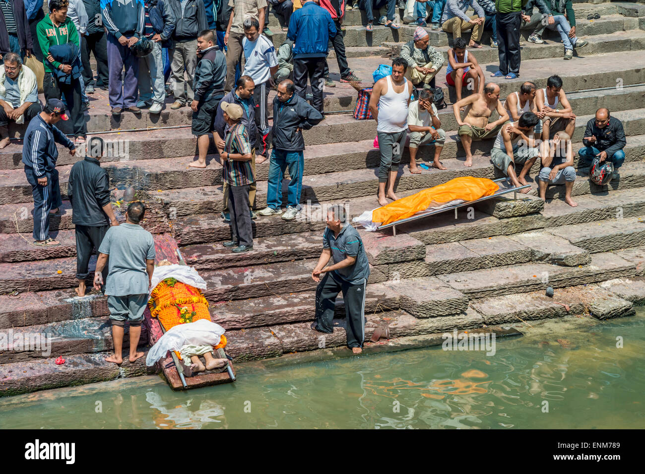 Pashupatinath Temple in Kathmandu. A dead body is washed by relatives - Stock Image