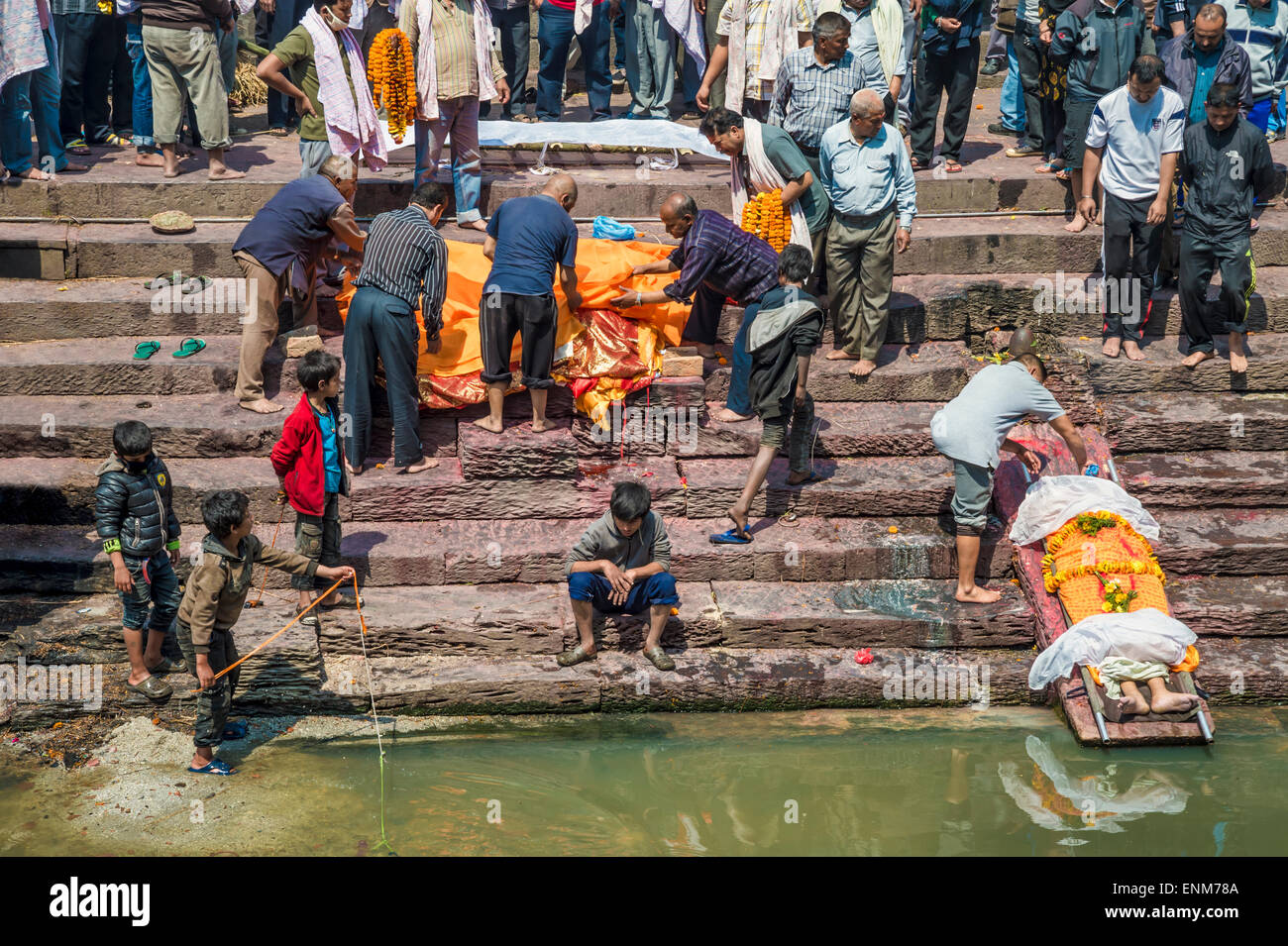 Pashupatinath Temple in Kathmandu. A dead body is washed by a relative - Stock Image