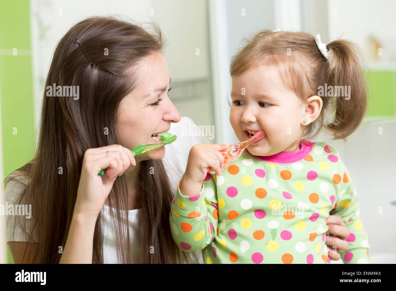 mother teaching daughter child teeth brushing in bathroom Stock Photo