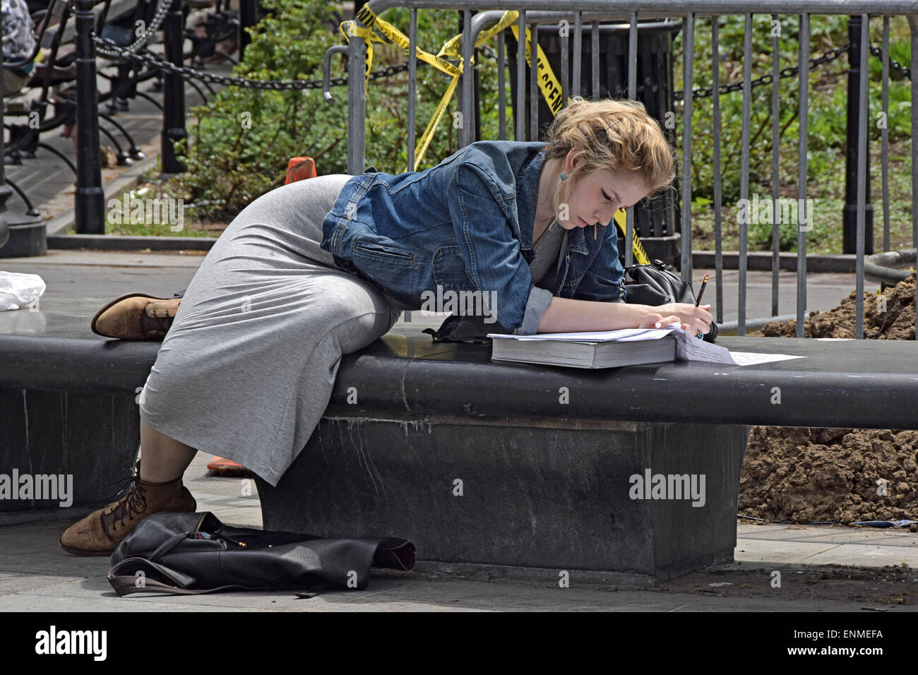 A pretty college student studying for exams outdoors in Washington Square Park in Greenwich Village, New York City - Stock Image