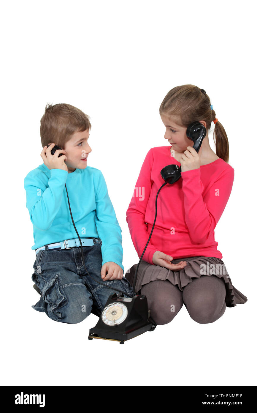 Kids using old-fashioned telephone - Stock Image